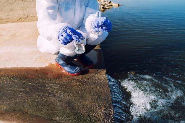 Ecologista irreconocible de pie donde las aguas residuales se encuentran con el río y toma muestras para determinar el nivel de contaminación y polución.