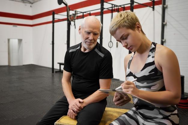 Edad madura, actividad, estilo de vida saludable y bienestar. atractivo hombre deportivo jubilado sentado en el gimnasio con su linda joven instructora que sostiene la pluma y el portapapeles, haciendo un plan de entrenamiento