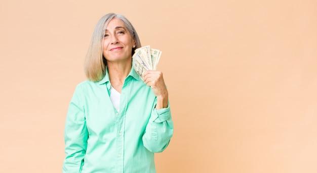 Edad media bonita mujer con billetes de dólar contra la pared del espacio de copia