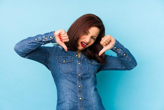 Edad media mujer latina aislada en azul mostrando el pulgar hacia abajo y expresando aversión.