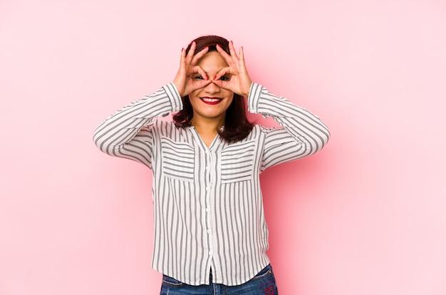 Edad media mujer latina aislada en una pared de color rosa que muestra signo bien sobre los ojos