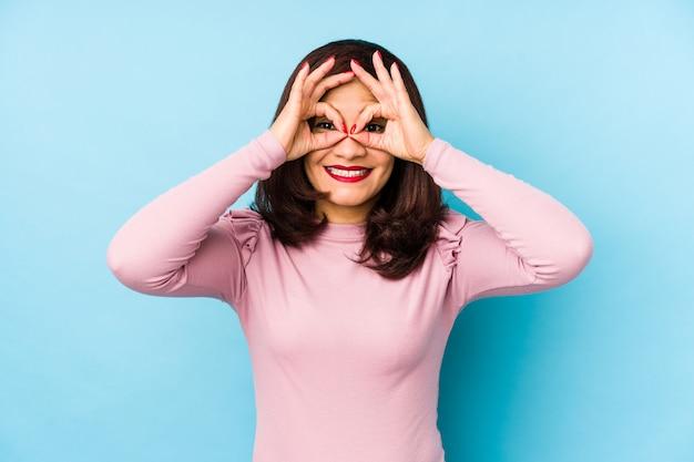 Edad media mujer latina aislada que muestra bien firmar sobre los ojos