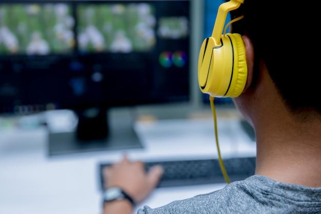 Edición de video por ordenador y auriculares amarillos.
