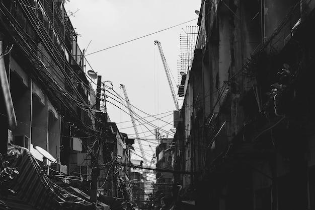 Edificio abandonado en barrios marginales con cables eléctricos desordenados en tono blanco