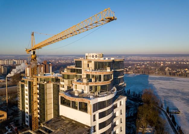 Edificio alto de apartamentos u oficinas en construcción, vista superior. grúa sobre fondo de espacio de copia de cielo azul brillante, paisaje de la ciudad que se extiende hasta el horizonte. drone fotografía aérea.
