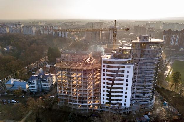 Edificio alto de apartamentos u oficinas en construcción, vista superior. grúa torre y paisaje de la ciudad que se extiende hasta el horizonte. drone fotografía aérea.