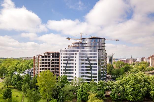 Edificio alto de apartamentos u oficinas sin terminar en construcción entre las copas de los árboles verdes.