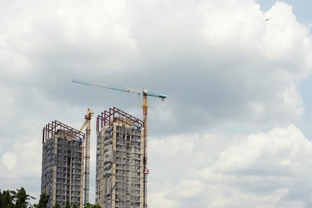 Edificio alto en construcción y tener una grúa en la obra.