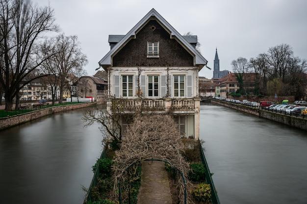 Edificio antiguo rodeado de agua y vegetación bajo un cielo nublado en estrasburgo en francia