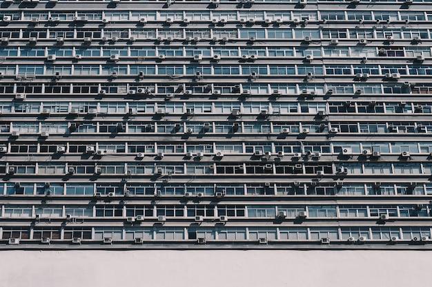 Edificio de apartamentos con muchas ventanas y aires acondicionados.