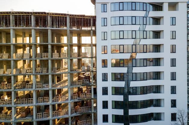Edificio de apartamentos u oficinas moderno, alto, de varios pisos, con ventanas brillantes y edificio sin terminar en construcción.