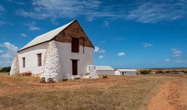 Edificio blanco en un campo de una granja en una zona rural bajo el cielo nublado
