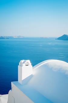 Edificio blanco contra el cielo azul y el mar en la isla de santorini, oia, grecia