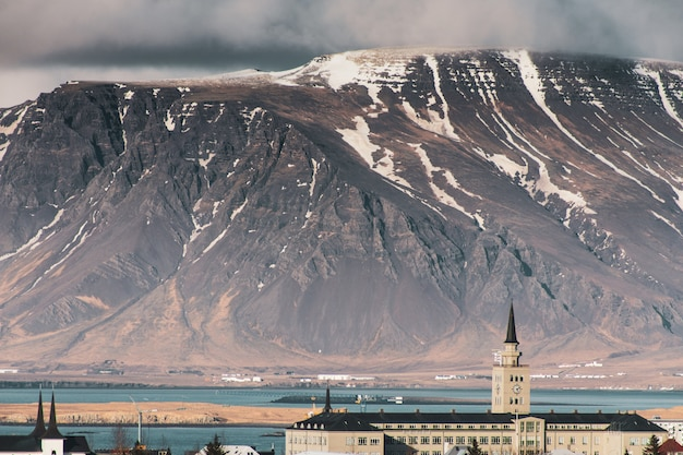 Edificio de la ciudad y una alta montaña rocosa y rígida con un glaciar en la parte superior