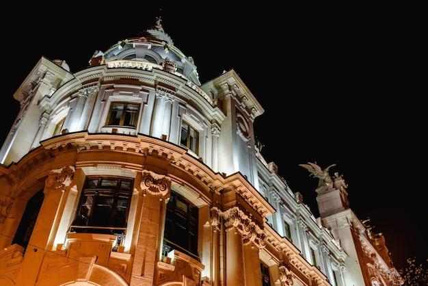 Edificio de correos en la plaza del ayuntamiento de la ciudad mediterránea de valencia, españa, iluminada por la noche.