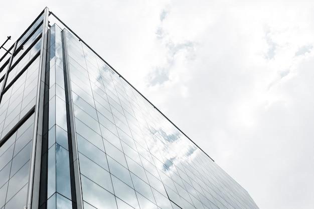 Edificio de cristal de ángulo bajo con nubes