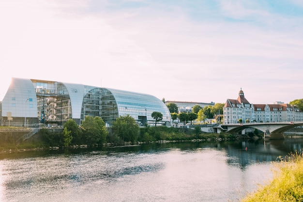 Edificio de cristal moderno y un edificio antiguo junto a un hermoso canal