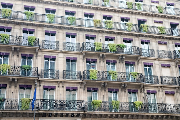 Edificio de fachada con ventanas y balcones. concepto de arquitectura y diseño. arquitectura europea. plantas en balcón. edificio arquitectónico de lujo. viajes y vacaciones. concepto de arquitectura.