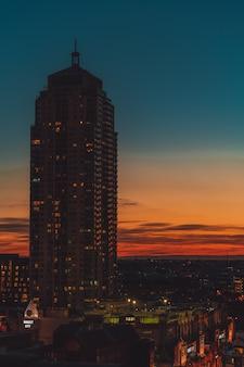 Edificio de gran altura con un cielo naranja y azul