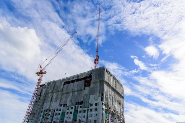 Edificio y grúa está en construcción con nubes y cielo azul