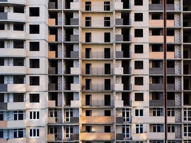 Edificio inacabado de varios pisos. edificio de ladrillo en construcción de gran altura, andamio, montacargas,