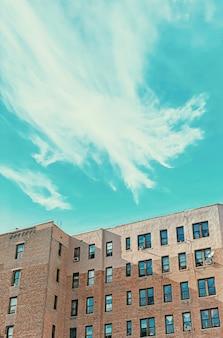 Edificio de ladrillo con ventanas y cielo azul.