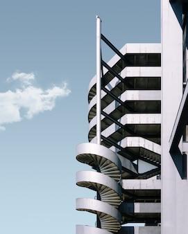 Edificio de metal y la escalera bajo el cielo azul.