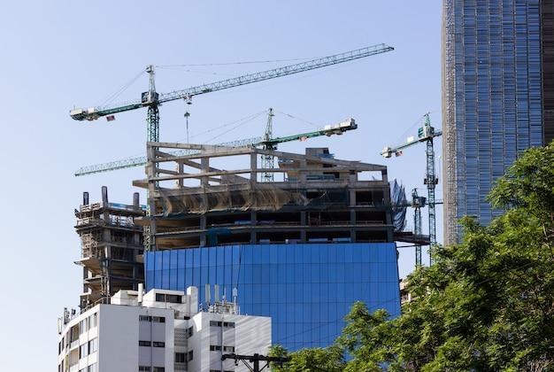 Edificio moderno en construcción con grúas en santiago ingeniería conceptos urbanísticos