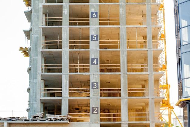 Edificio moderno en detalle de construcción, estructura de hormigón, aberturas de ventanas y andamios.