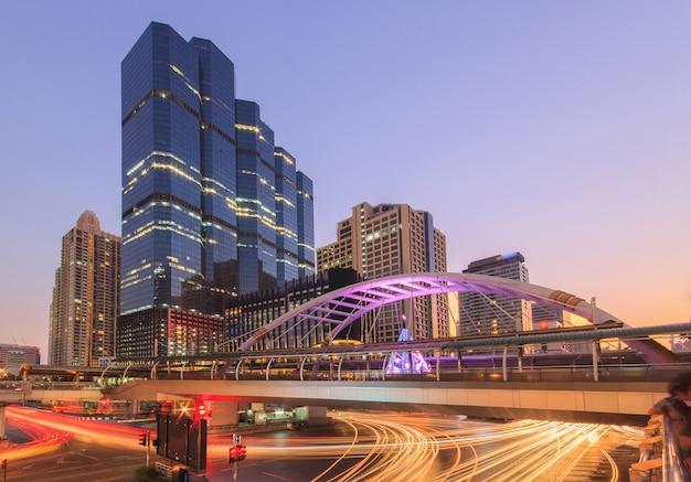 Edificio moderno de noche. tráfico en el distrito financiero la estación de skytrain chong nonsi