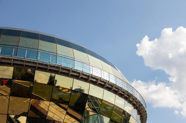 Edificio moderno con la parte superior esférica cubierta con paneles de vidrio dorado contra el cielo despejado.