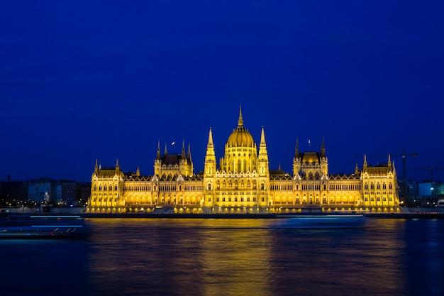 Edificio del parlamento iluminado de budapest en la noche con el cielo oscuro y la reflexión en el río danubio