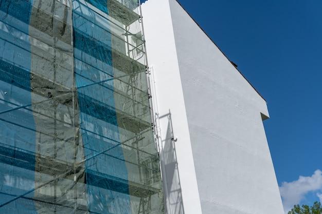 Edificio pintado con andamios metálicos.