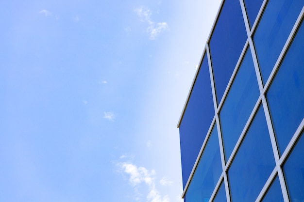 Edificio de rascacielos de cristal con fondo de cielo azul nublado