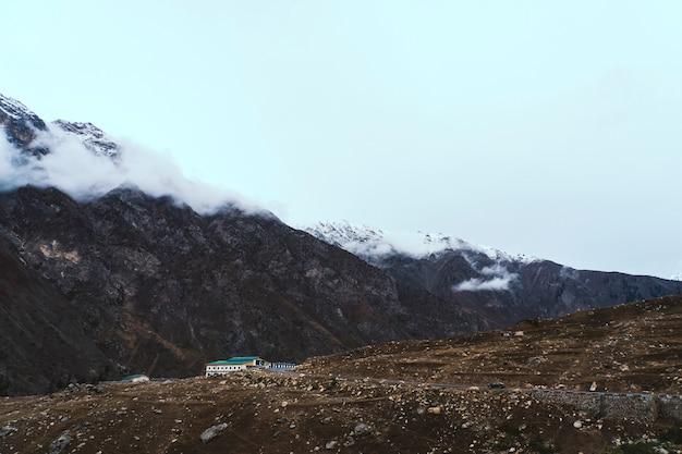 Edificio solitario junto a las montañas con bandera pakistaní.