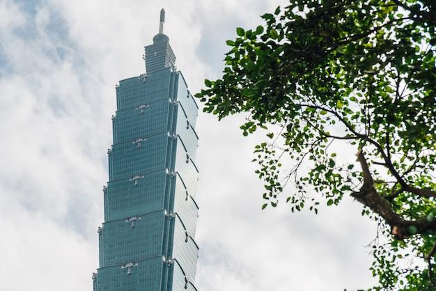 Edificio taipei 101 con ramas de árboles en el lado derecho con cielo azul brillante y nubes en taipei, taiwán.