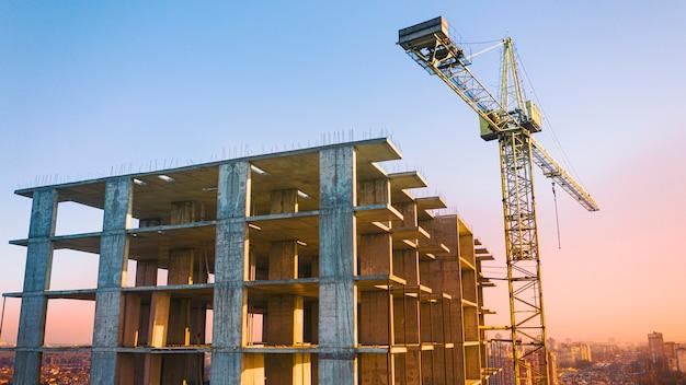 Edificio de varios pisos, grúa torre y obra de construcción, vista superior. al atardecer.