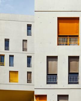 Edificios blancos con cortinas de colores en las ventanas.