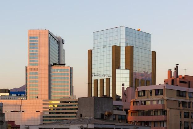 Edificios de espejo de cristal del distrito financiero junto a los residenciales al atardecer en santiago de chile.