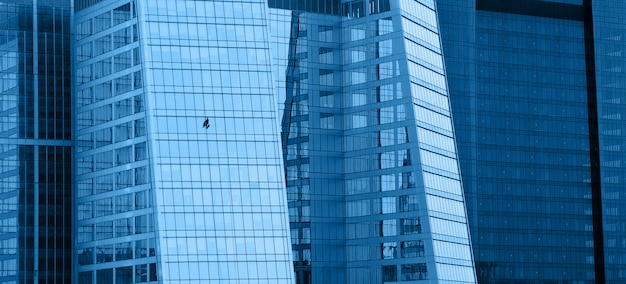 Edificios de oficinas modernos de vidrio con limpiacristales, fondo horizontal panorámico