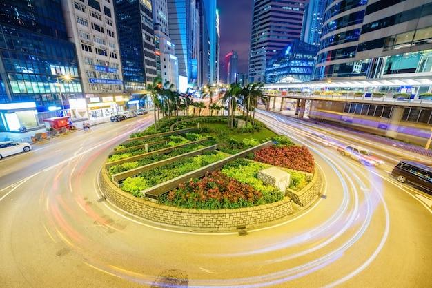 Los edificios de oficinas de rascacielos y el tráfico ocupado en la carretera de la carretera con los coches borrosos senderos de luz.