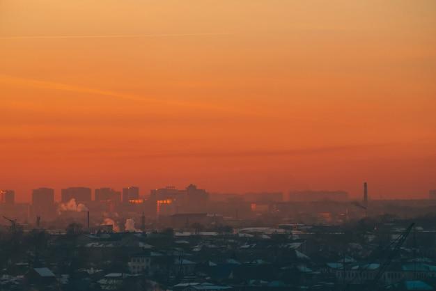 Edificios urbanos de gran altura detrás de casas privadas en la puesta del sol.