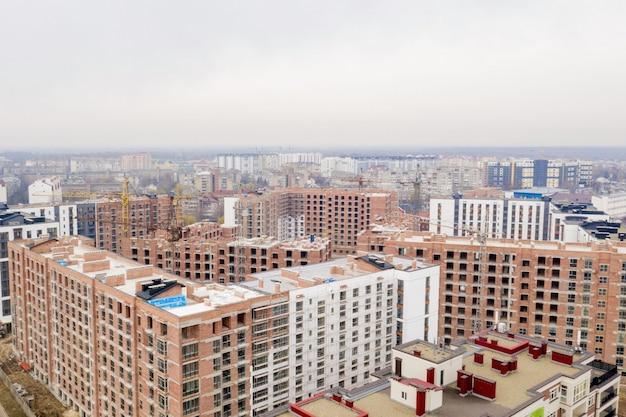Edificios de varios pisos de gran altura en construcción. grúas torre cerca del edificio. actividad, arquitectura, proceso de desarrollo.
