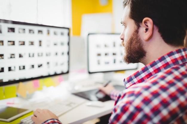 Editor concentrado en fotografías en computadora en la oficina creativa