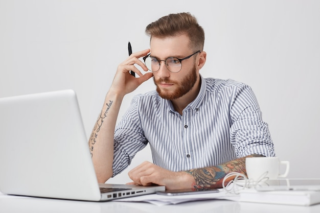 Editor masculino creativo con tatuajes, mira con confianza a la pantalla de la computadora portátil, trabaja duro, rodeado de un teléfono inteligente moderno