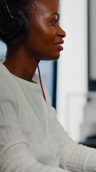 Editor de video africano con auriculares escuchando música mientras edita imágenes