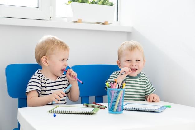 Educación y afición. dos niños gemelos rubios pintan con rotulador.