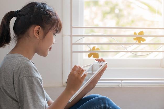 Educación, aprendizaje, estudio en línea joven asiática hermosa estudiante uso tableta para buscar