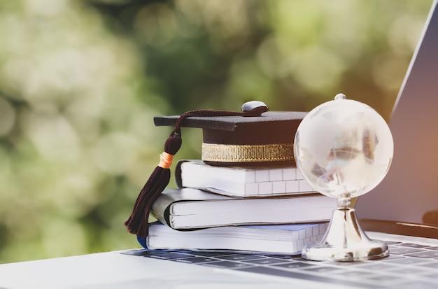 Educación en crystal global, gorra de graduación en el libro de texto superior con computadora de teclado