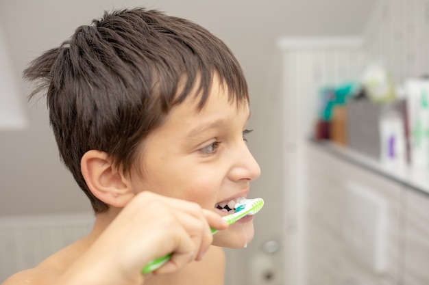Educación dental en la familia, un adolescente con alegría de 10 años, lavándose los dientes con pasta de dientes y un cepillo de dientes en el baño